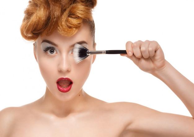 Retrato de belleza de mujer bonita con pincel para maquillaje