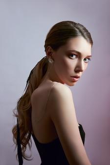 Retrato de belleza de una mujer con cabello largo y aretes en sus oídos