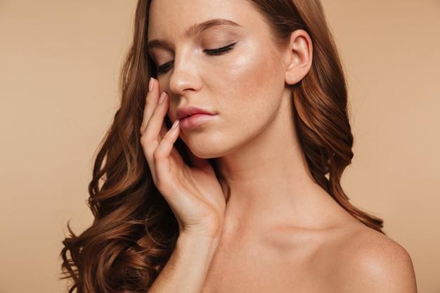 Retrato de belleza de mujer de jengibre con el pelo largo de cerca posando con el brazo cerca de la cara