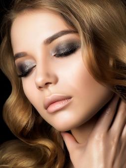 Retrato de belleza de mujer joven con maquillaje dorado tocando su cuello