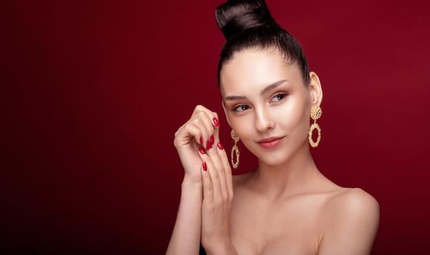 Retrato de belleza de mujer posando con aretes de oro