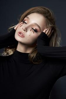 Retrato de belleza mujer rubia con maquillaje, cosmética natural, cara de niña de piel limpia delicada, ropa negra.