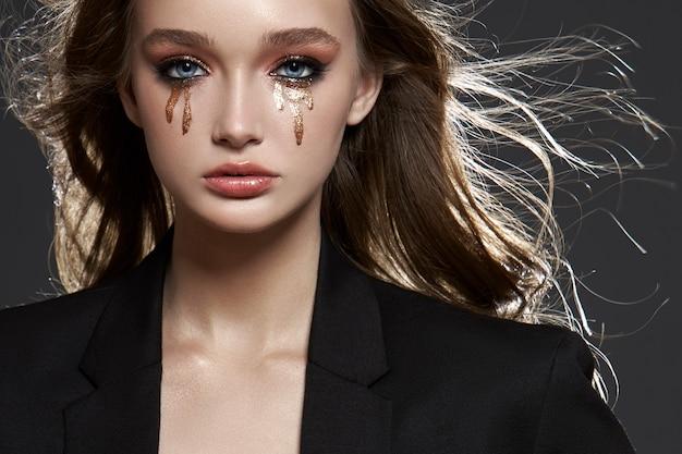 Retrato de belleza mujer rubia con maquillaje y grandes ojos azules, cosmética natural, piel limpia y delicada de la carita de niña, ropa negra