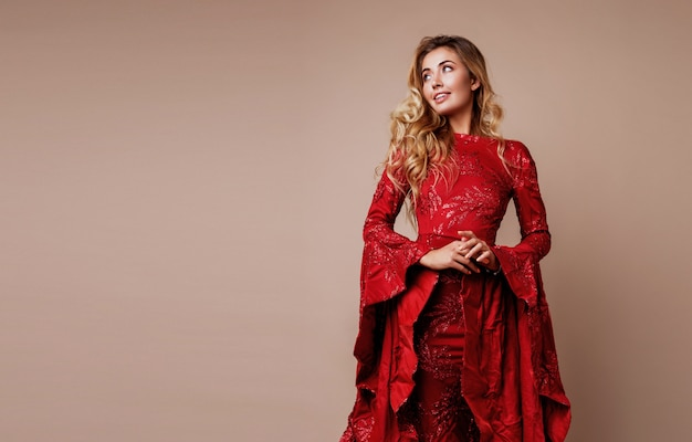 Retrato de belleza de mujer rubia perfecta con labios carnosos, maquillaje natural posando en increíble vestido rojo de lujo con lentejuelas y mangas anchas. las manos cerca de la cara.
