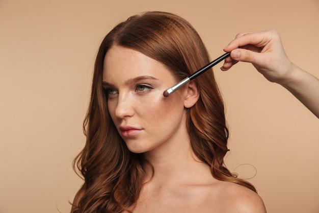 Retrato de belleza de mujer tranquila de jengibre con cabello largo mirando a otro lado mientras alguien aplica cosméticos con pincel