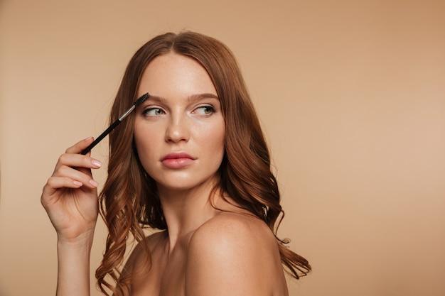 Retrato de belleza de mujer tranquila de jengibre con cabello largo mirando a otro lado y posando de lado mientras se peina las cejas con un cepillo