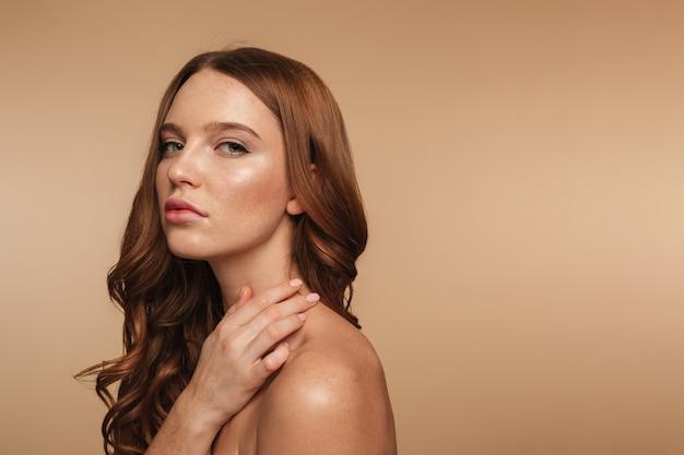 Retrato de la belleza de la mujer tranquila de jengibre con el pelo largo posando de lado y mirando