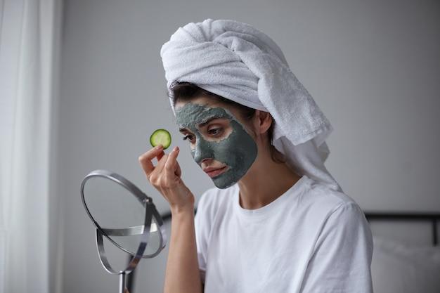 Retrato de belleza de mujer tranquila de pelo oscuro joven atractiva en mascarilla hidratante con pepino fresco en su mano mirando en el espejo, manteniendo los labios doblados mientras posa sobre el interior de la casa