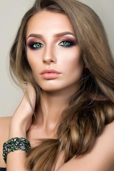 Retrato de belleza de niña bonita con ojos verdes con pulsera verde y tocar su cabello. maquillaje de ojos ahumados modernos