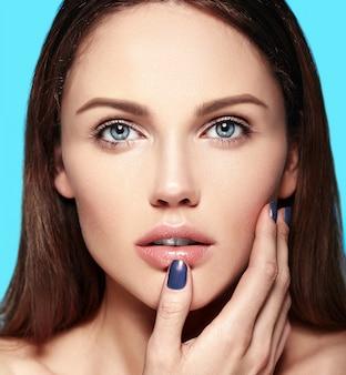 Retrato de belleza de primer plano de glamour de hermosa sensual modelo caucásica joven con maquillaje desnudo tocando su piel limpia perfecta aislada sobre fondo azul