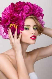 Retrato de belleza de primer plano de niña bonita con flores en el pelo con lápiz labial rosa brillante, tocando su peinado. maquillaje de verano moderno y brillante