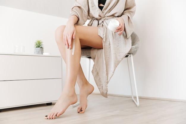 Retrato de belleza recortada de mujer delgada con piel suave y saludable, aplicando crema corporal en las piernas en casa