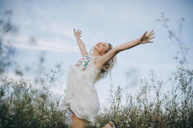 Retrato de una belleza rubia con ojos azules y cabello largo en la cabeza caminando en campo con flores blancas