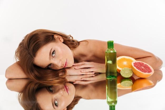 Retrato de belleza de sonriente mujer de jengibre con el pelo largo acostado en la mesa de espejo con frutas y una botella de lotin mientras mira
