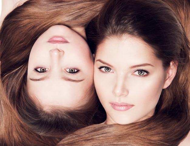 Retrato de los bellos rostros de madre e hija de 8 años con cabello largo