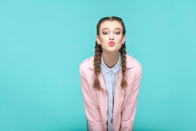 Retrato de besos feliz de hermosa linda chica de pie con maquillaje y peinado de coleta marrón en camisa azul claro a rayas chaqueta rosa. interior, tiro del estudio aislado en fondo azul o verde.