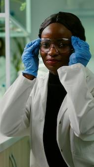 Retrato de biólogo africano en bata blanca mirando a cámara trabajando en laboratorio de microbiología