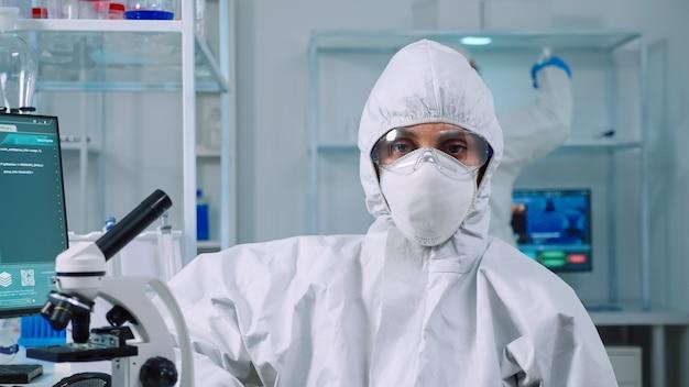 Retrato de biólogo con exceso de trabajo mirando a la cámara en el moderno laboratorio equipado. equipo de científicos que examinan la evolución del virus utilizando herramientas de alta tecnología y química para la investigación científica y el desarrollo de vacunas.