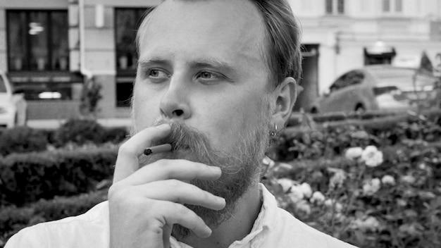 Retrato en blanco y negro de elegante joven con barba fumando cigarrillos en el parque.