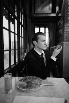 Retrato en blanco y negro del empresario sentado en el restaurante
