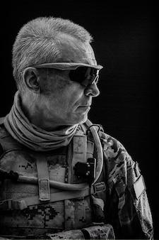 Retrato en blanco y negro de las fuerzas especiales veterano de pelo blanco con uniformes de campo, negro
