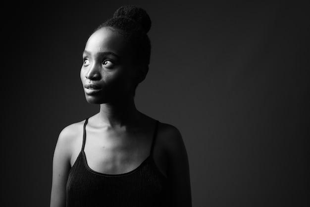 Retrato en blanco y negro de joven hermosa mujer africana pensando