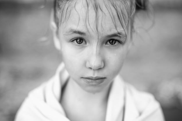 Retrato en blanco y negro de niña con cabello húmedo y toalla caliente en la playa