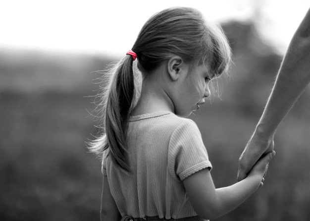 Retrato en blanco y negro de niña con una mano de su madre
