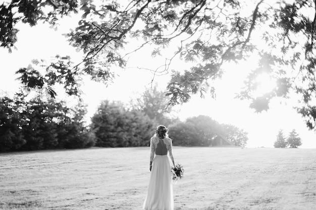 Retrato en blanco y negro de una novia de pie en el campo al atardecer