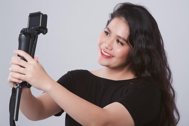 Retrato del blogger femenino asiático joven que graba el video del vlog con la cámara de la acción que transmite en vivo en estudio. mujer grabando contenido para su vlog.
