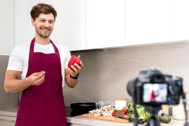 Retrato de blogger grabando video de cocina en casa
