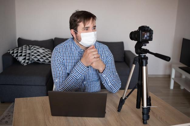 Retrato de blogger man review grabación de video en casa influyente en línea vlogger medios sociales concepto de transmisión en vivo, coronavirus, enfermedad, infección, cuarentena, máscara médica