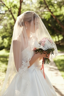 Retrato de boda de una novia mujer bajo un velo blanco.