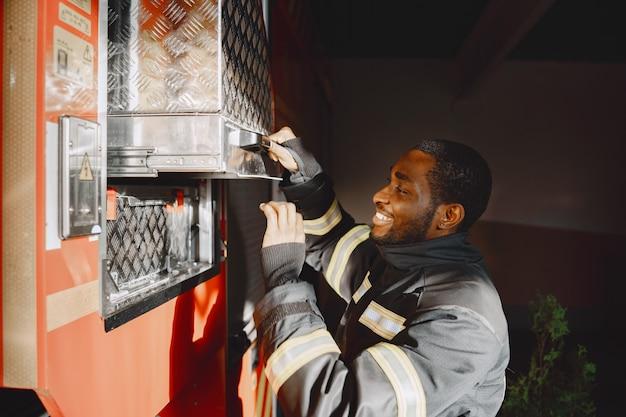 Retrato de un bombero de pie delante de un camión de bomberos