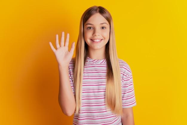 Retrato de bonita hermosa niña preadolescente saludando a mano de onda sobre fondo amarillo brillante