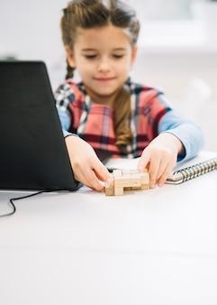 Retrato borroso de una niña jugando con rompecabezas de madera en el escritorio blanco