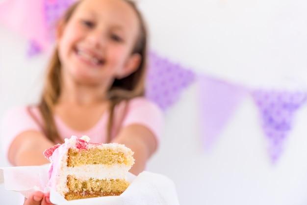 Retrato borroso de una niña sonriente que ofrece rebanada de pastel