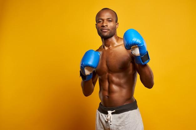 Retrato del boxeador atlético afroamericano en guantes azules.