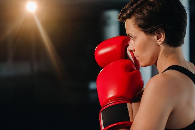 Retrato de una boxeadora en guantes rojos en el gimnasio durante el entrenamiento