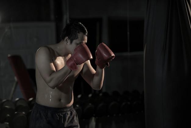 Retrato de un boxeo practicante del hombre asiático joven en un bolso de perforación en el gimnasio.
