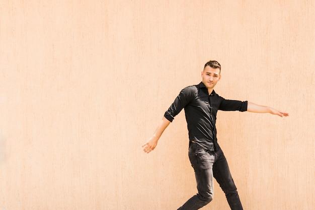 Retrato de breakdancer masculino joven contra la pared