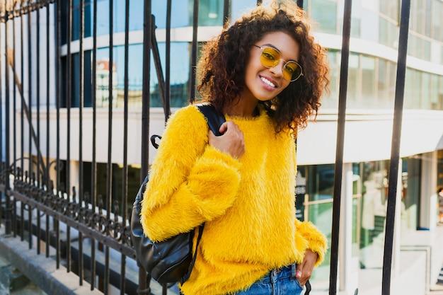 Retrato brillante al aire libre de niña feliz con mochila y de pie en urbano