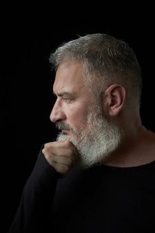 Retrato de un brutal hombre de cabello gris con una exuberante barba gris y cara estricta sobre un fondo negro, enfoque selectivo