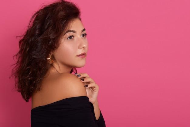 Retrato de buena mujer caucásica mirando a un lado con expresión facial pensativa, de pie contra la pared rosa, manteniendo la mano sobre los hombros. copie el espacio.