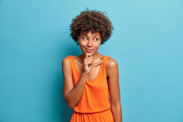 Retrato de buena mujer de pelo rizado sostiene la barbilla y mira con expresión pensativa de ensueño a un lado