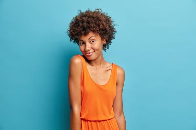 Retrato de buena mujer de pelo rizado se ve con expresión satisfecha
