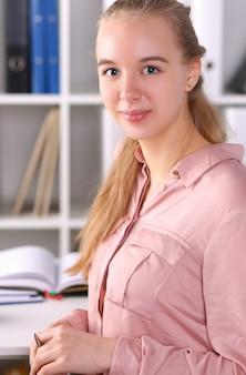 Retrato de businesslady sonriente con alegría. linda mujer alegre sentada en el lugar de trabajo. secretaria trabajando en oficina. concepto de reunión de negocios