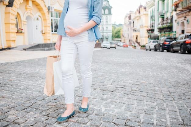 Retrato de un cabello negro feliz y orgullosa mujer embarazada en una ciudad en la calle. imagen de primer plano de modelo femenino tocando su vientre con las manos