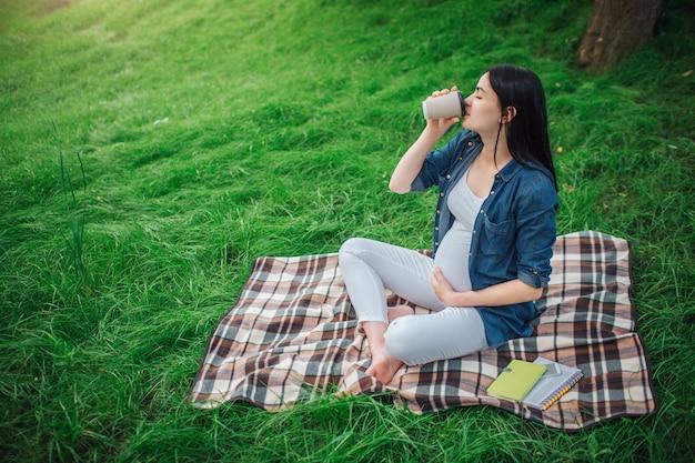 Retrato de un cabello negro feliz y orgullosa mujer embarazada en una ciudad en el parque. foto de modelo femenino tocando su vientre con las manos. la modelo femenina está sentada en el césped y tomando café o té.