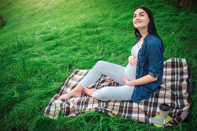 Retrato de un cabello negro feliz y orgullosa mujer embarazada en una ciudad en el parque. foto de modelo femenino tocando su vientre con las manos. la modelo femenina está sentada sobre la hierba.